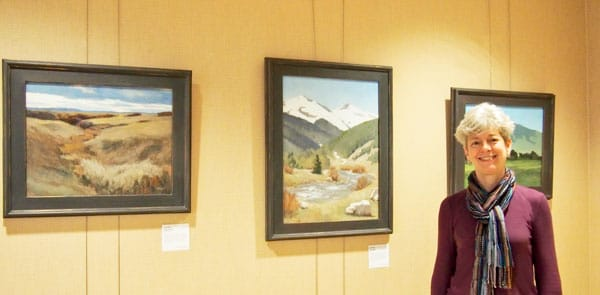 Photo of Sue with paintings that hang in Porter Adventist Hospital.