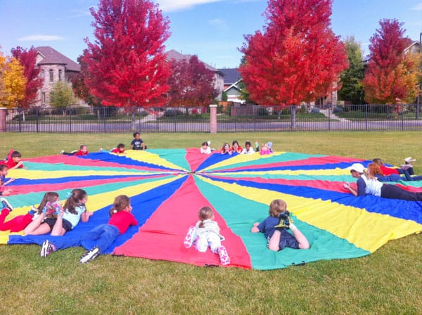 Picture of kids playing on a parachute