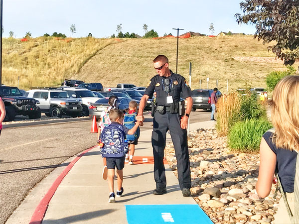 Photo of police officer greeting student