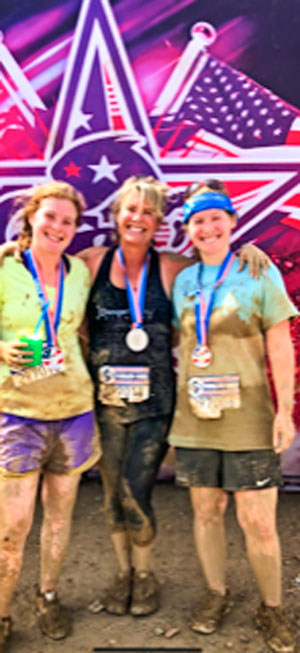 Photo of Ronda Gutierrez daughters run a mud obstacle course race together.