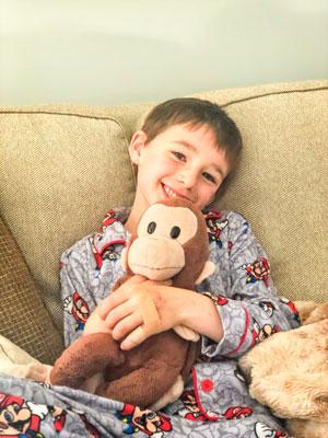 Reid Berry cuddling Curious George.