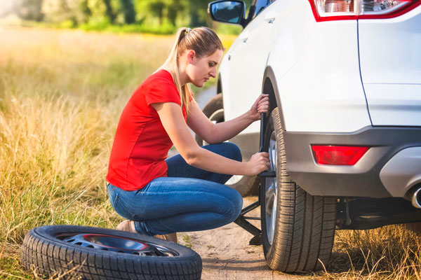 Photo or woman changing flat tire