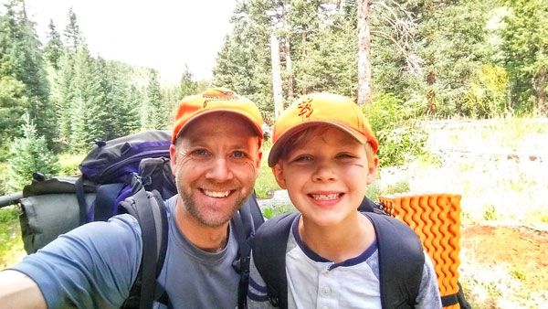 Photo of son and father backpacking