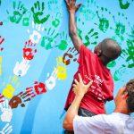 Photo of Ghanaian boy adding handprint to school