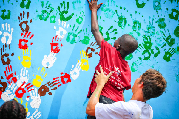 Photo of Ghanaian boy adding handprint to school