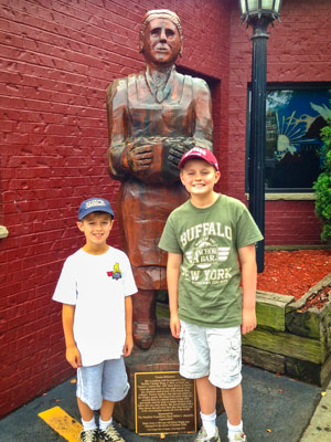Matthew and Ryan Tierney stand in front of the statue of Teressa Bellissimo