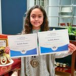 Photo of Isabella proudly celebrating her spelling bee win.