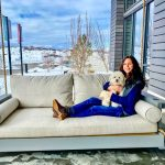 Photo of Dana Jevarjian and her dog, Benji, on the porch swing outside The Exchange Coffee + Conversation