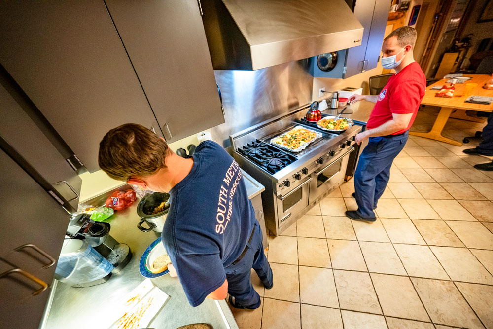 Photo of SMFR Lt. Dustin Searle (right) helps prepare a meal with a crewmate.