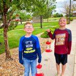 Photo of Eli Claypool and Ayden Godina with hummingbird feeders
