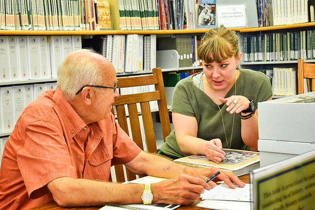 Photo of Joe Gschwendtner works with Douglas County Libraries Archivist Alyssa Carver on historical research.