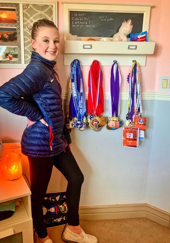 Photo of Autumn Hall posing at home with her medals.