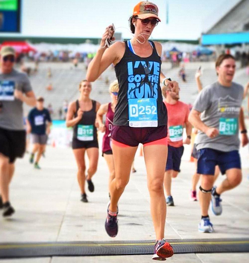 Photo of Lindsey Gerstner as she crosses the finish line of the BolderBoulder.