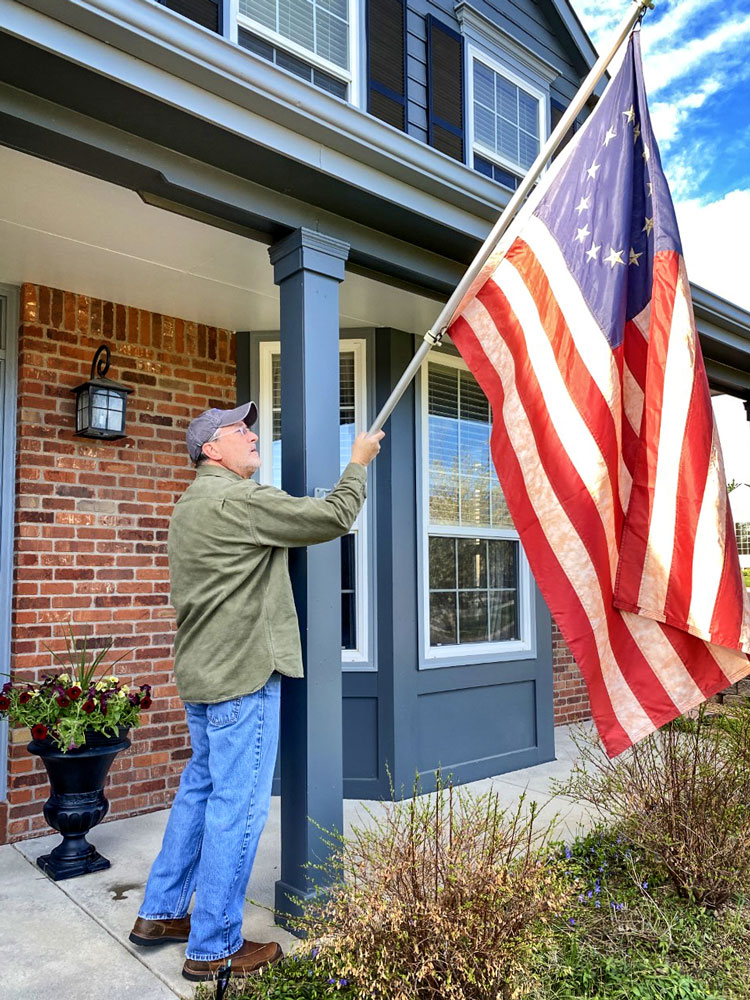 Photo of Michael Conner putting up U.S. flag.