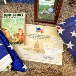 Photo of Michael Conner's Boy Scout handbook and other memorabilia.