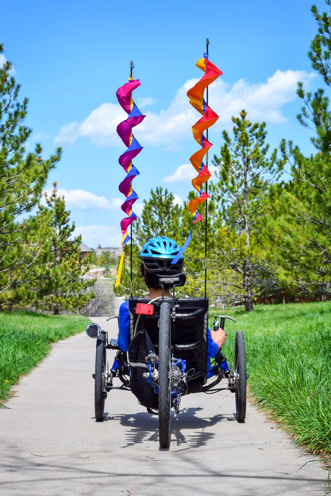 Photo of Carol Gransee and her flags on recumbant bike.