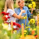 Photo of Amy Dismuke and her daughter Ann inspecting flowers.