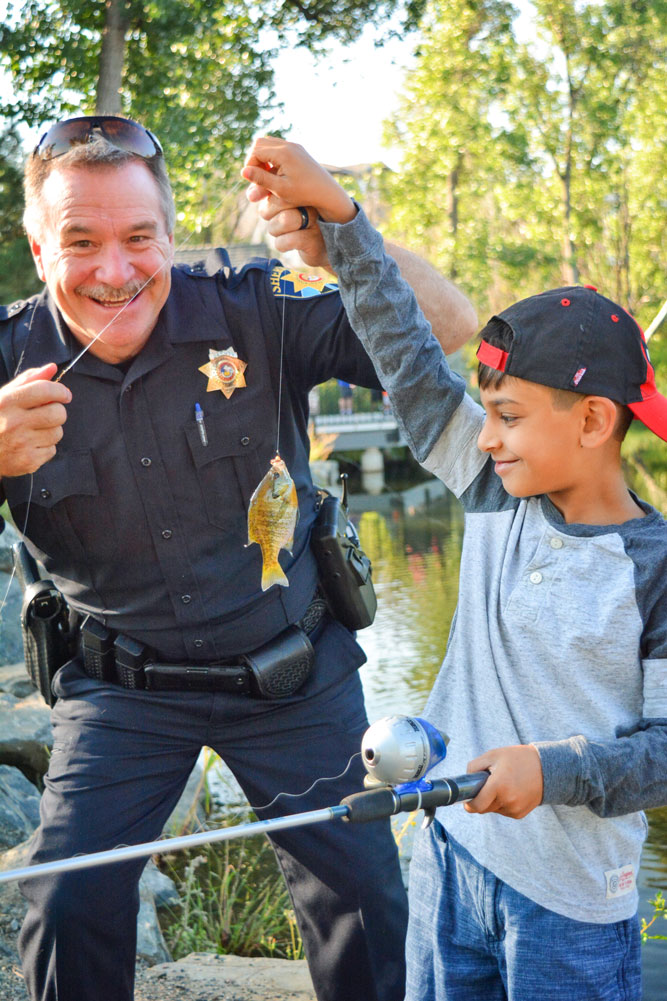 Photo of Deputy Brian McKnight shares a smile and a fish with a local child.