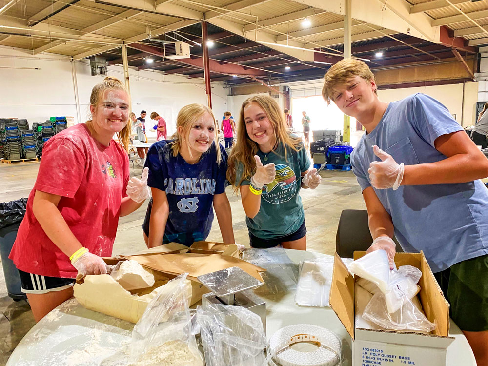 Photo of Junior Katelyn Pocock, sophomore Kyia Sparks, senior Hailey Arbuckle, and Everett Brothers, a visiting sophomore from Springville High School in Springville, Utah, got a little messy repackaging flour for Metro Caring's food bank.