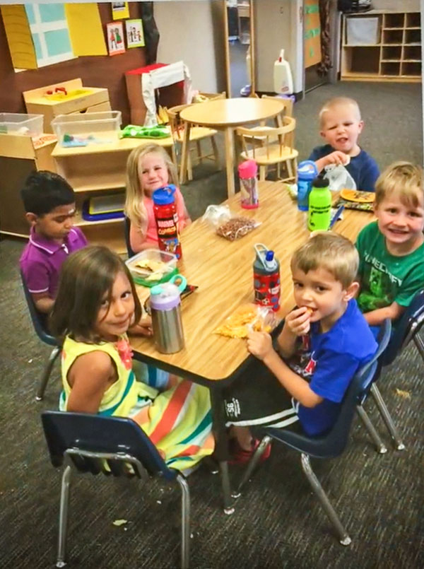 Photo of Caleb M. (top right) making a face at the camera during preschool snack